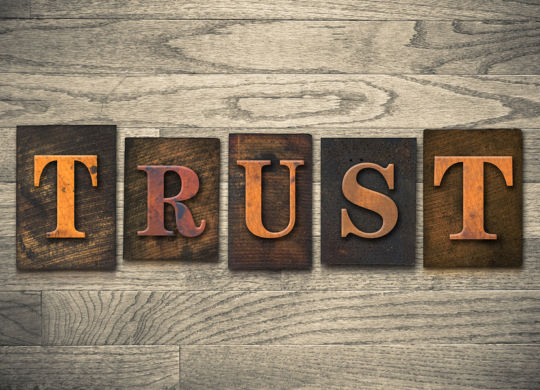 "The word ""TRUST"" written in vintage wooden letterpress type"